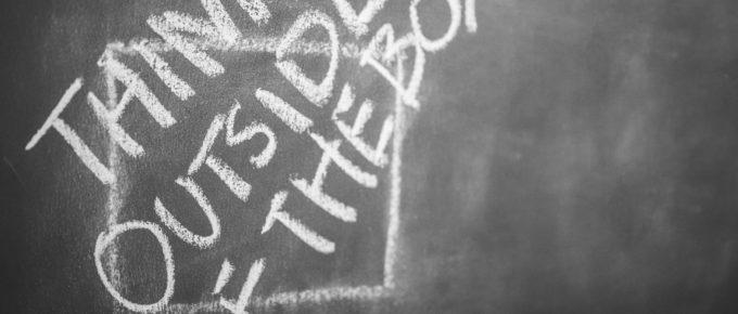 """""""Think Outside The Box"""" written on a chalkboard"""