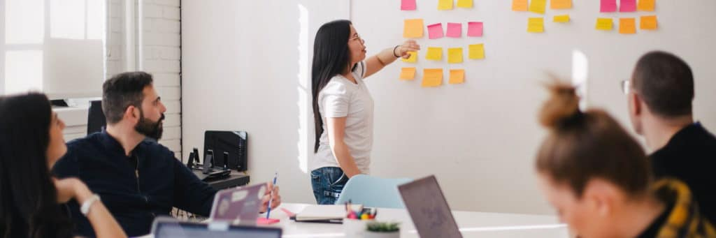 Woman placing sticky notes on a wall during a business strategy workshop