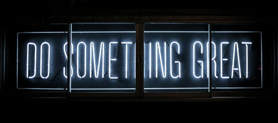 "Neon sign on a wall with the text ""do something great"""