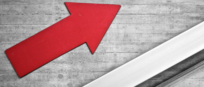 A red arrow painted on a wall showing an up and to the right trend