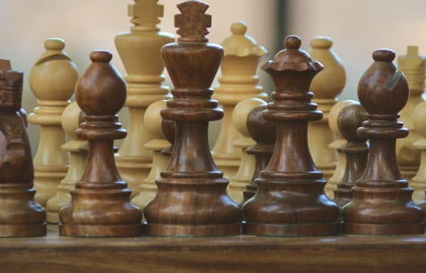 Close up of wooden chess pieces arranged on a game board