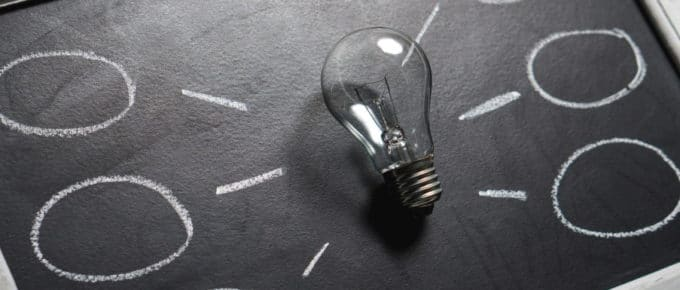A clear lightbulb placed on a chalkboard