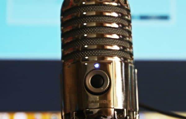 Close up on a podcast interview microphone with a computer screen in the background, out of focus